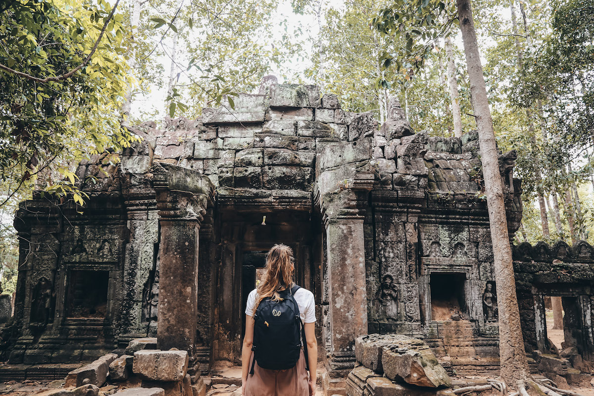 Girl looks at temple in Angkor Wat complex, Siem Reap