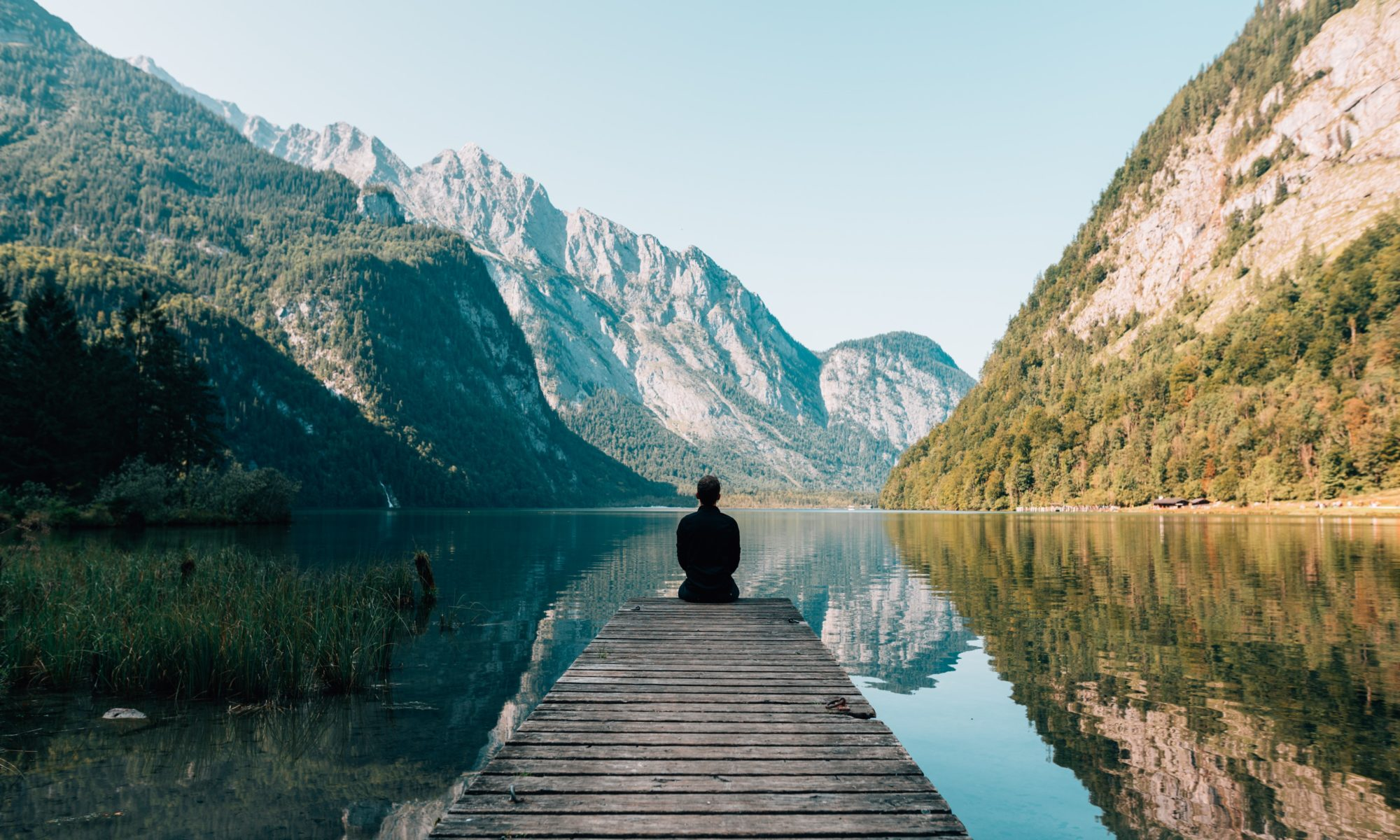 Solo man sits on a dock by lake