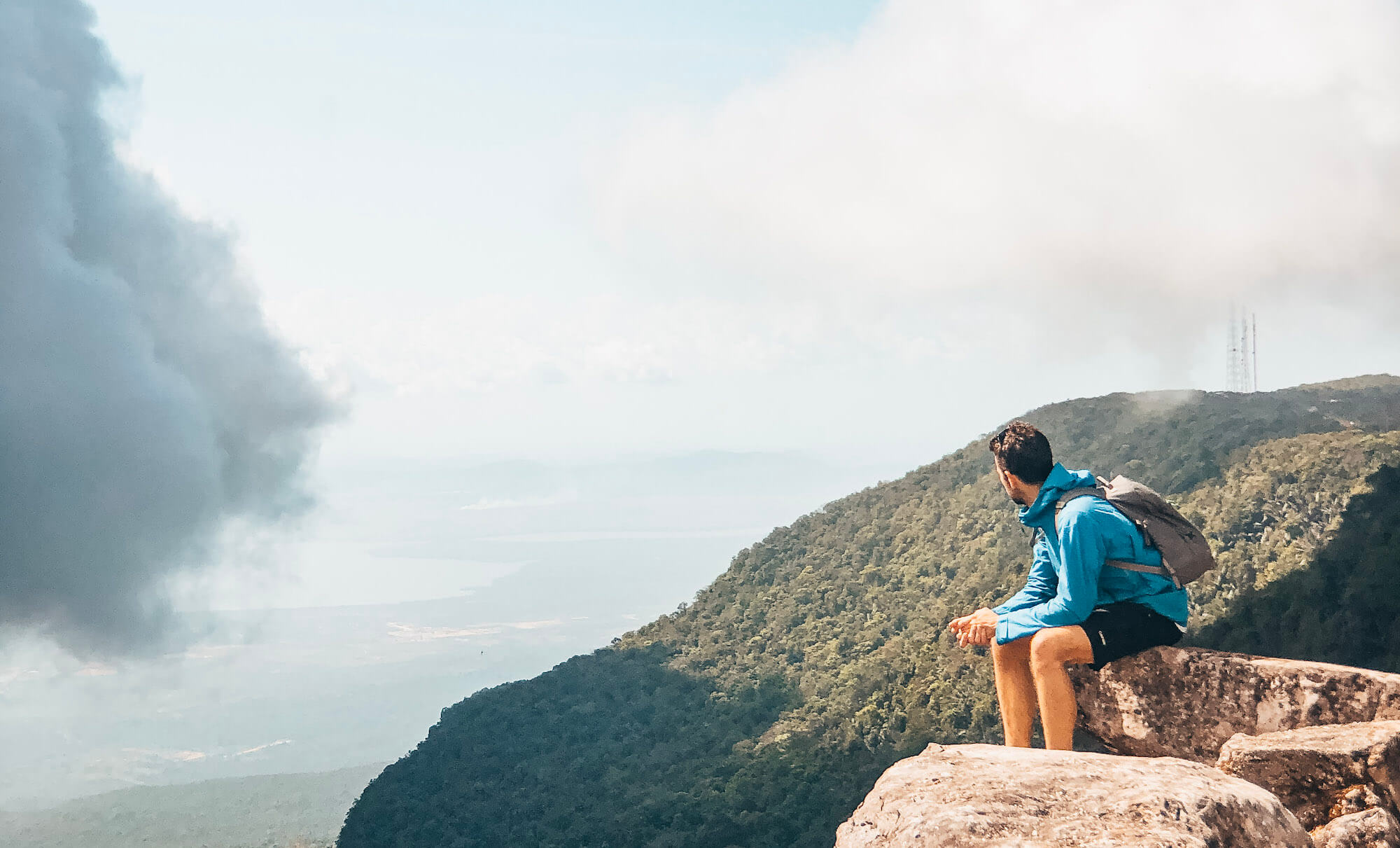 Man sits on rock overlooking hills and cloud on Bokor Mountain